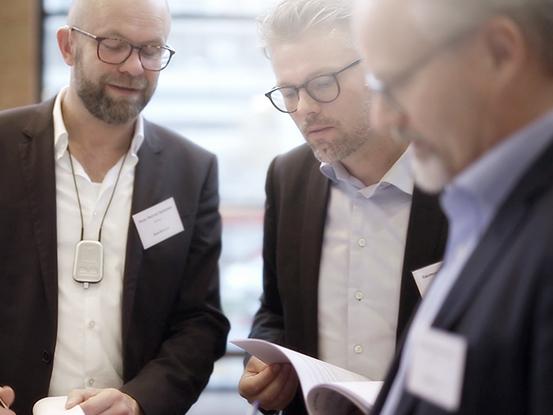 Tre mænd i jakkesæt kigger på et dokument